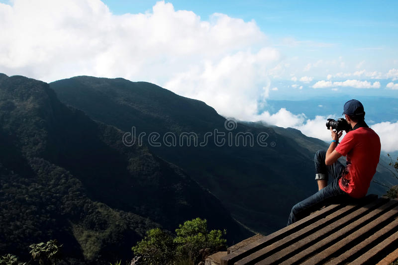 Man on the cliff edge photographing nature. Plateau Horton , place the End of the world , Sri Lanka stock photos
