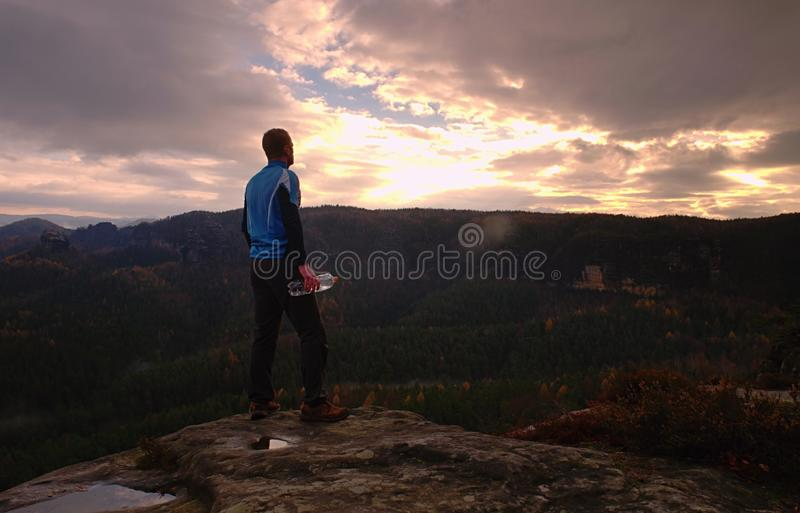 Man on a cliff edge on top of mountain with gorgeous view. Man on a cliff edge on the top of mountain with gorgeous view and drink water vacation traveler sunset stock photos