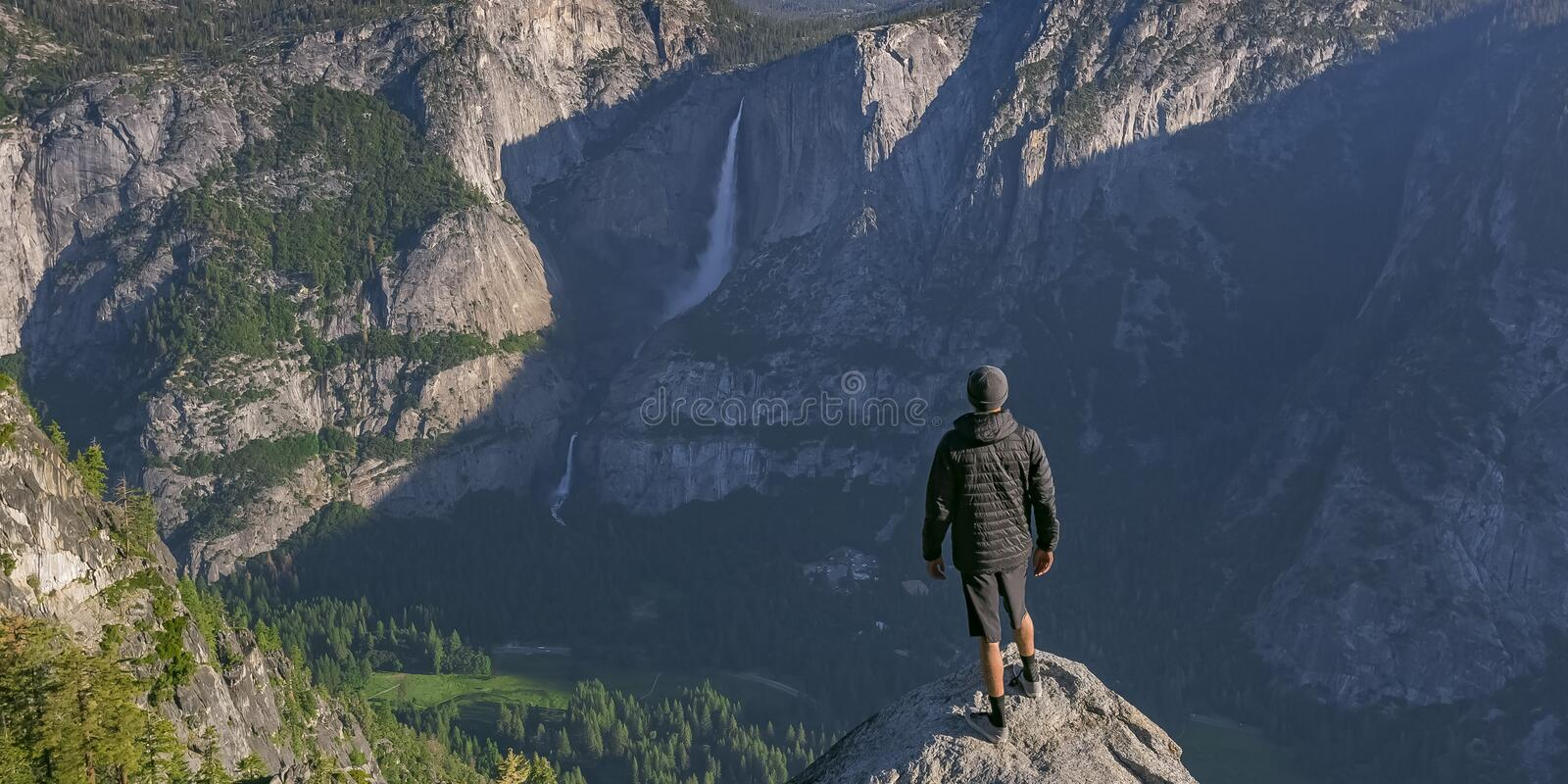 Man on cliff overlooking Yosemite Falls and valley royalty free stock photos