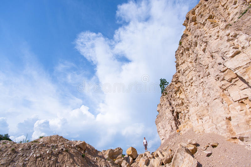 Man on the cliff of white stones royalty free stock image