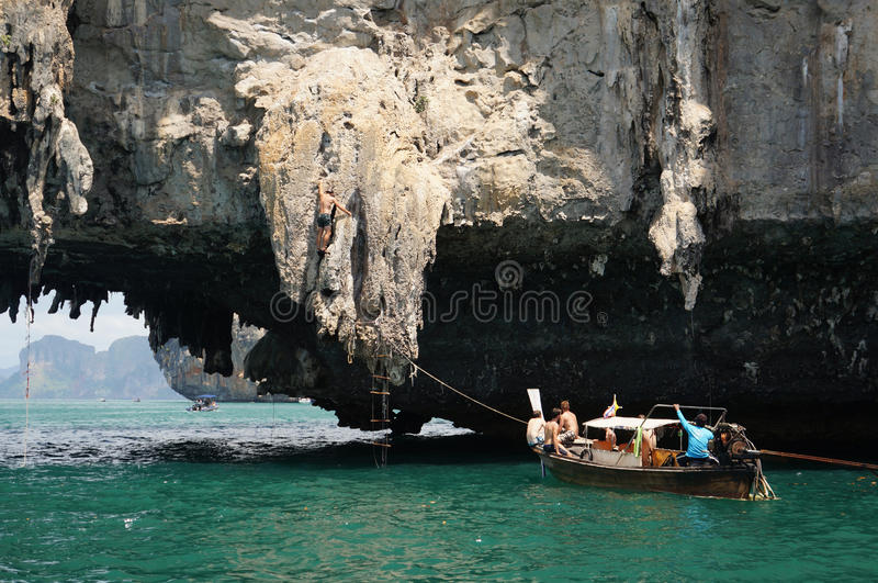 Man climb rock cliff. An unidentified man climb rock cliff while his friends cheer up in the boat in Thailand royalty free stock photo