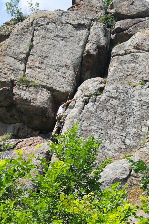 Man climber climbing up on rock stock photography