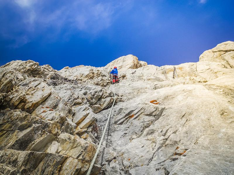 A man climber climbs the rocky ledges to the top. The concept of extreme recreation and adventure. stock photo