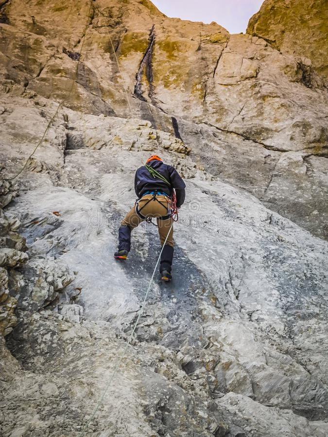A man climber climbs the rocky ledges to the top. The concept of extreme recreation and adventure. stock photography