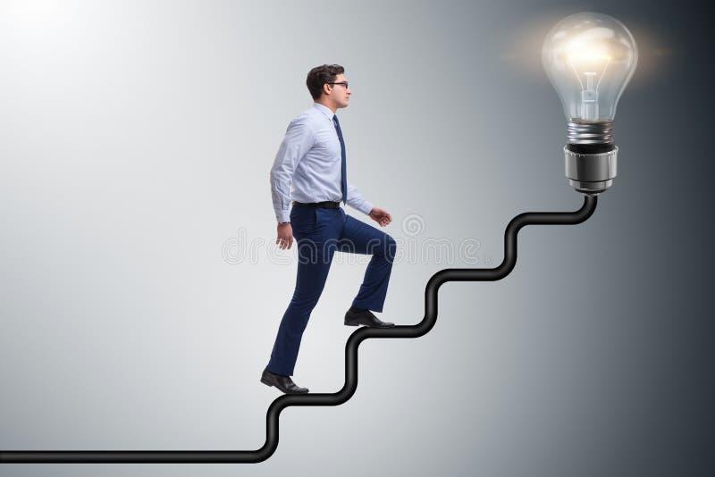 The man climbing career ladder towards bright light bulb stock photo
