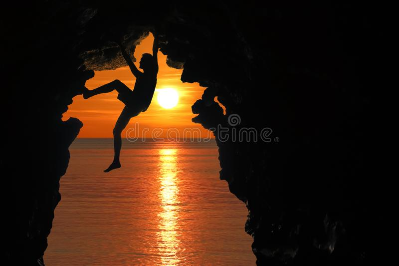 Man climbing in the cave by the sea with red sky and sunset royalty free stock images