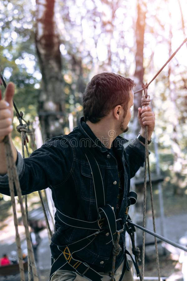 Man, climbing gear in an adventure park are engaged in rock climbing or pass obstacles on the rope road, arboretum, insurance, stock photography