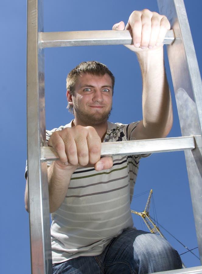 Man climbing ladder stock photos