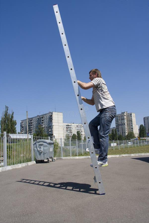 Man climbing ladder stock photography