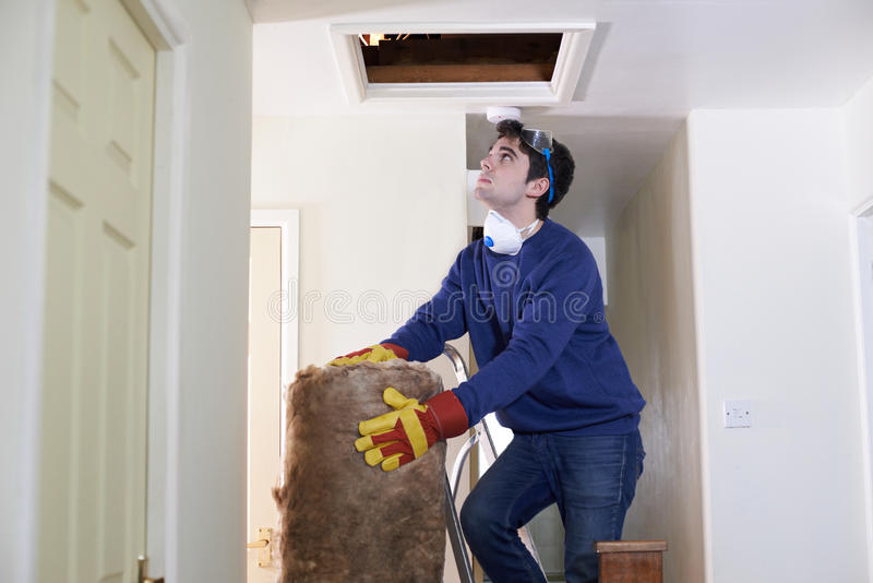 Man Climbing Into Loft To Insulate House Roof. Man Climbs Into Loft To Insulate House Roof stock image