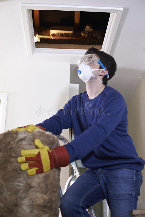 Man Climbing Into Loft To Insulate House Roof. Man Climbs Into Loft To Insulate House Roof stock photography