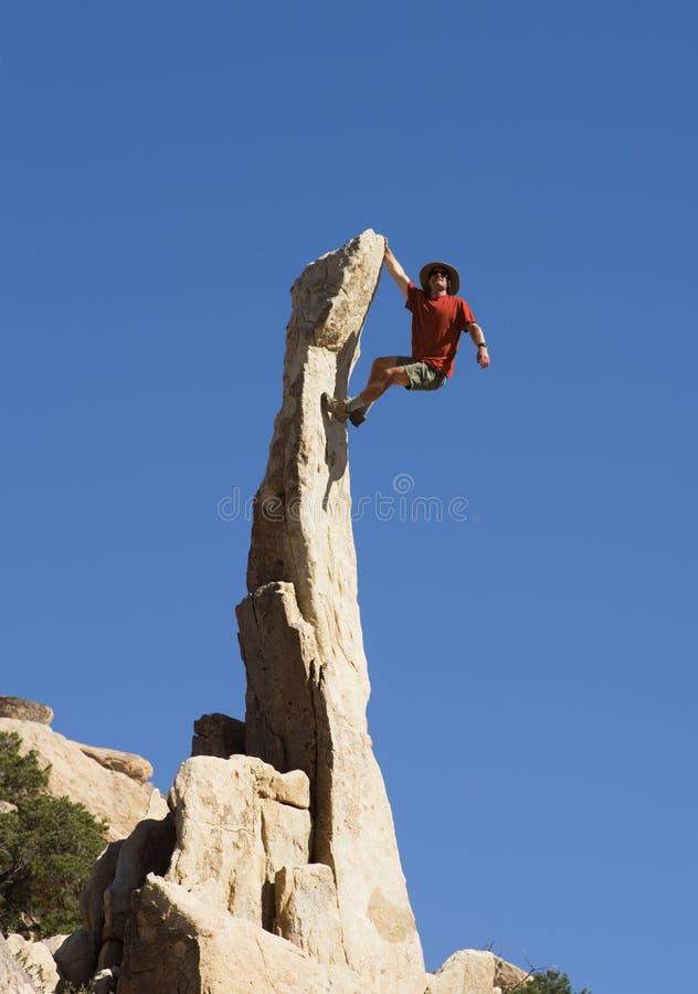 Man Climbing Rock Spire stock photos