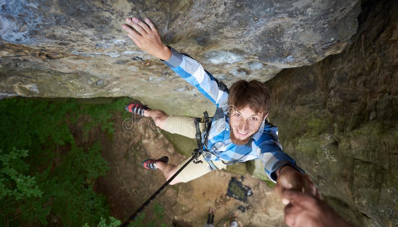 Young climber smiling, hanging on rope on rock. Man falling down from the cliff holding friend`s hand royalty free stock images