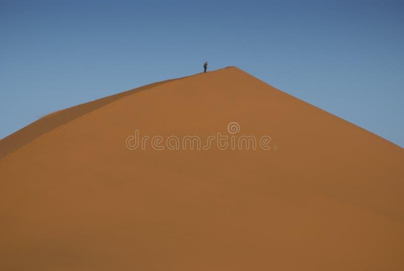Man climbing sand dune stock image