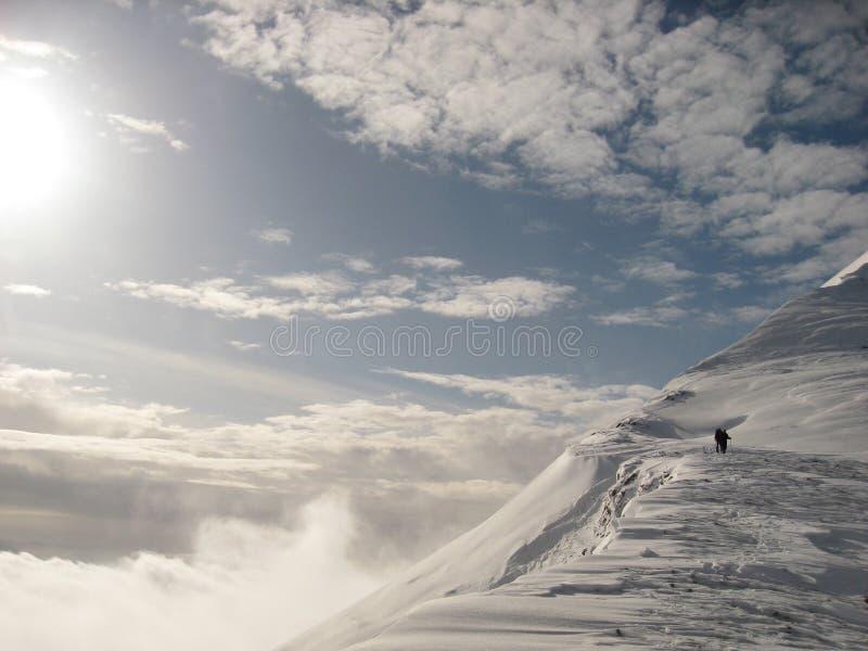 Man climbing snowy mountain royalty free stock photos
