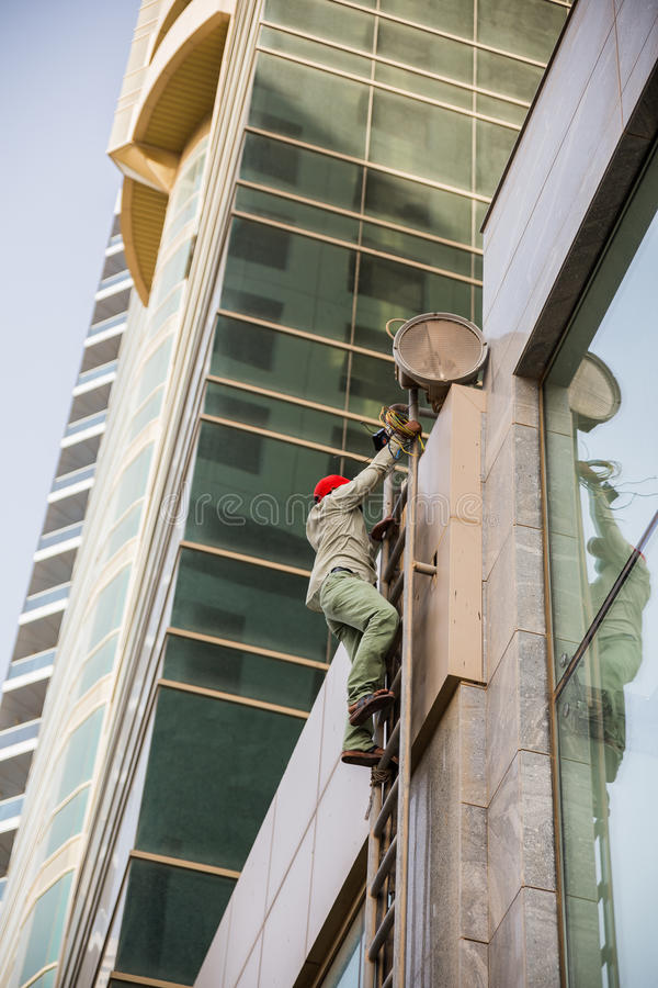 Man Climbing to The Top of The Building for Services at Dubai stock images