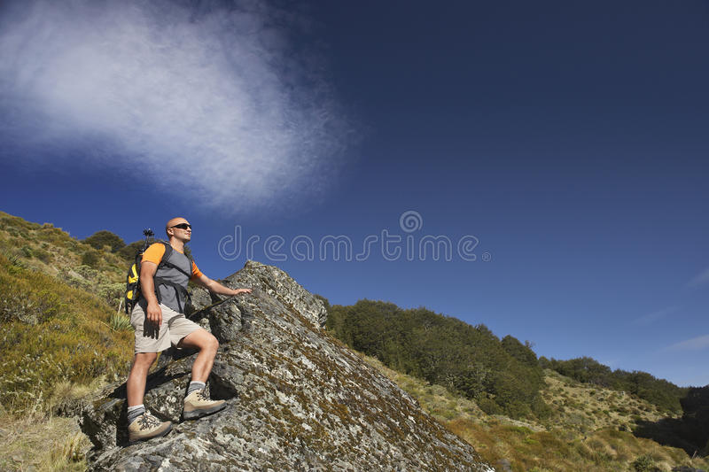 Man Climbing Up Boulder In Forest Valley