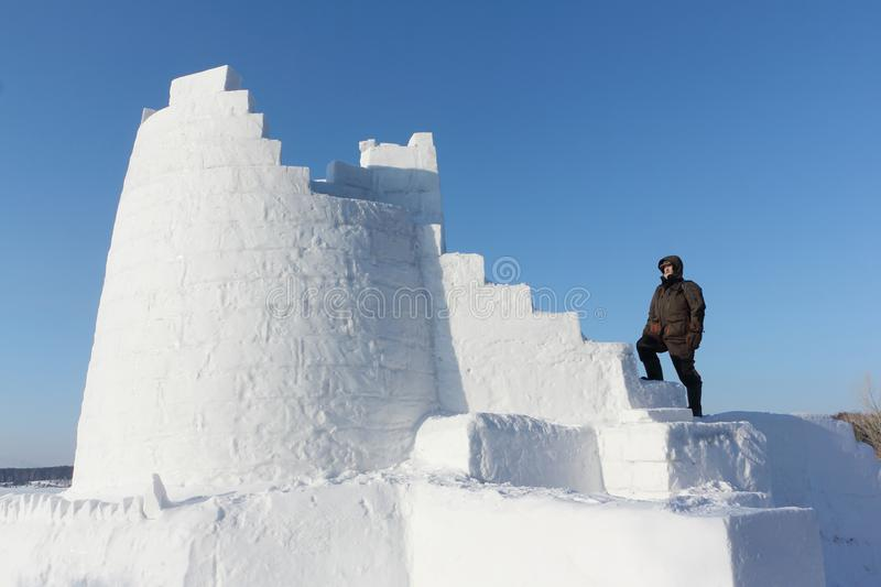 Man climbing up the steps of a snow tower, Novosibirsk, Russia stock photos