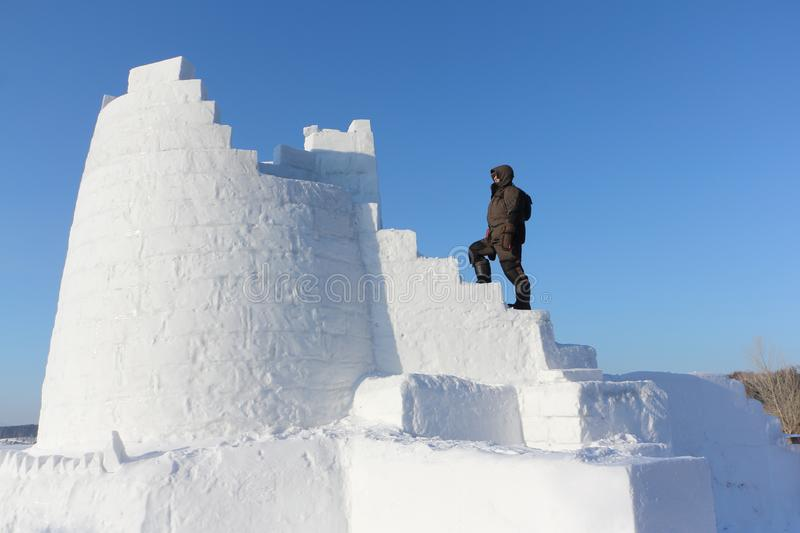 Man climbing up the steps of a snow tower, Novosibirsk, Russia stock photo