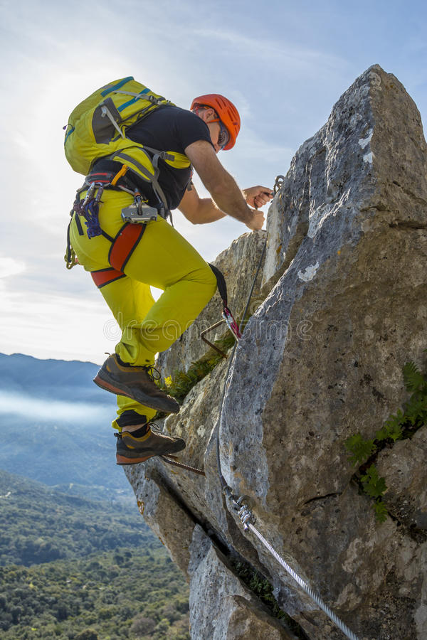 Man climbing a via ferrata stock images