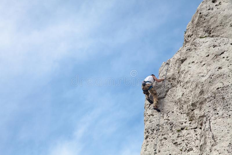 Man climbs to the top of the mountain. Rock climbing with belaying. royalty free stock image