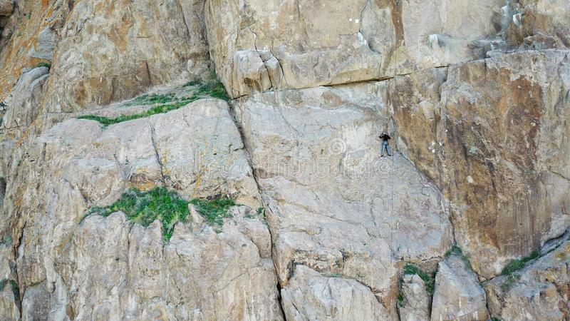 A man climbs up the cliff. Active leisure and sports. Climb up the rock. Shooting from the air. Aerial photography. Extreme, active rest, freedom. Beautiful stock images