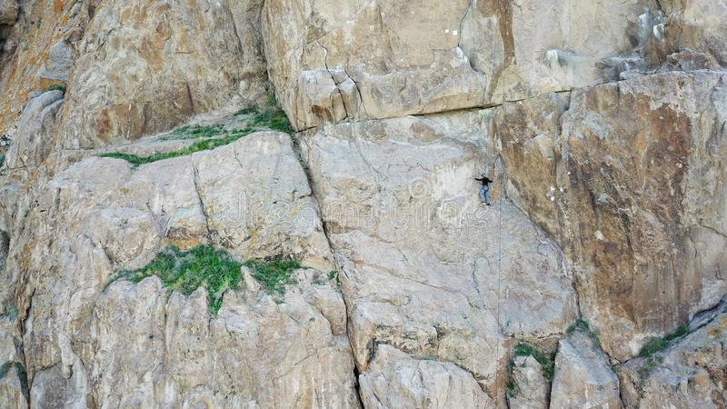 A man climbs up the cliff. Active leisure and sports. Climb up the rock. Shooting from the air. Aerial photography. Extreme, active rest, freedom. Beautiful royalty free stock photo