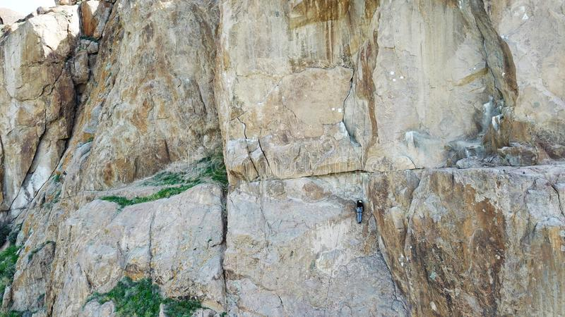 A man climbs up the cliff. Active leisure and sports. Climb up the rock. Shooting from the air. Aerial photography. Extreme, active rest, freedom. Beautiful royalty free stock photography
