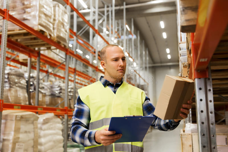 Man with clipboard in safety vest at warehouse. Wholesale, logistic, people and export concept - man with clipboard and box in reflective safety vest at stock photos