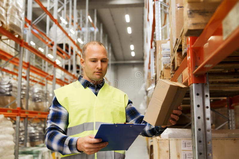 Man with clipboard in safety vest at warehouse. Wholesale, logistic, people and export concept - man with clipboard and box in reflective safety vest at stock photo
