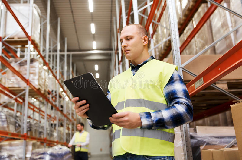 Man with clipboard in safety vest at warehouse. Wholesale, logistic, people and export concept - men with clipboard in reflective safety vest at warehouse stock photo