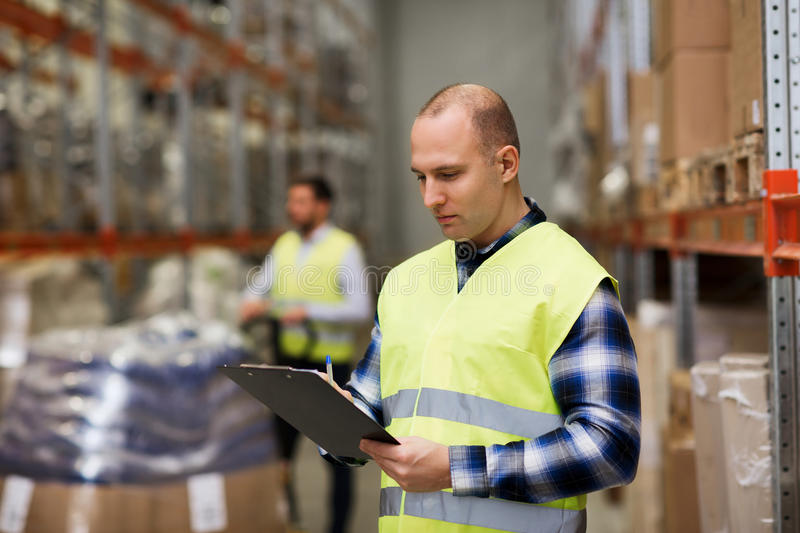 Man with clipboard in safety vest at warehouse. Wholesale, logistic, people and export concept - men with clipboard in reflective safety vest at warehouse royalty free stock photography
