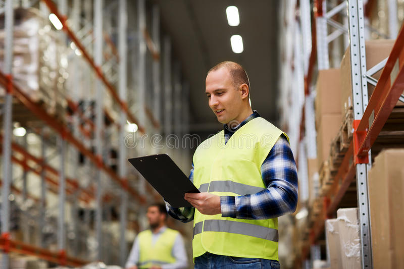 Man with clipboard in safety vest at warehouse. Wholesale, logistic, people and export concept - men with clipboard in reflective safety vest at warehouse royalty free stock image
