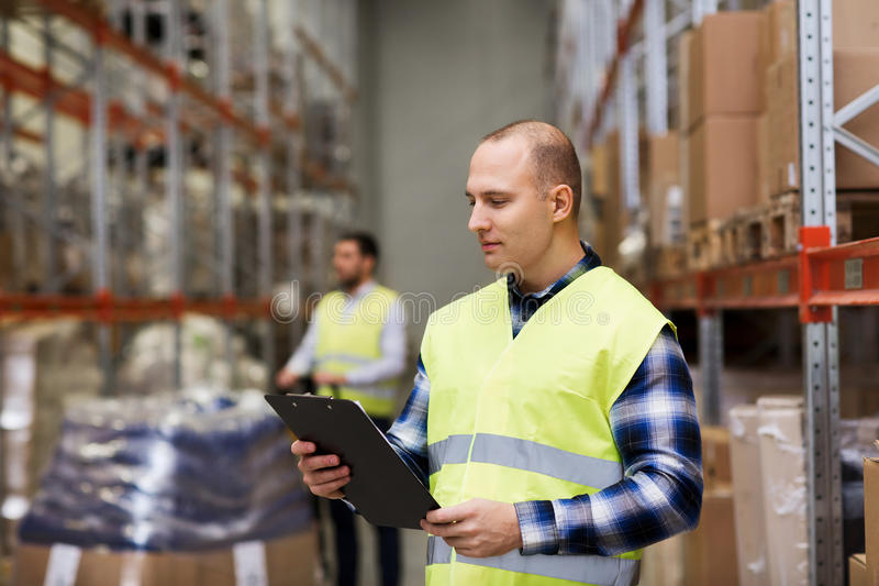Man with clipboard in safety vest at warehouse. Wholesale, logistic, people and export concept - men with clipboard in reflective safety vest at warehouse royalty free stock photos