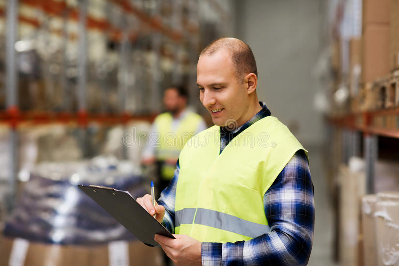 Man with clipboard in safety vest at warehouse. Wholesale, logistic, people and export concept - men with clipboard in reflective safety vest at warehouse royalty free stock images