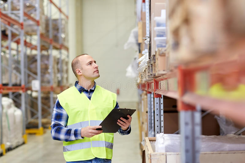 Man with clipboard in safety vest at warehouse. Wholesale, logistic, people and export concept - man with clipboard in reflective safety vest at warehouse stock photo