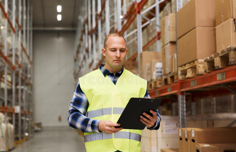 Man with clipboard in safety vest at warehouse. Wholesale, logistic, people and export concept - man with clipboard in reflective safety vest at warehouse royalty free stock photos