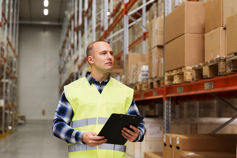 Man with clipboard in safety vest at warehouse. Wholesale, logistic, people and export concept - man with clipboard in reflective safety vest at warehouse stock images