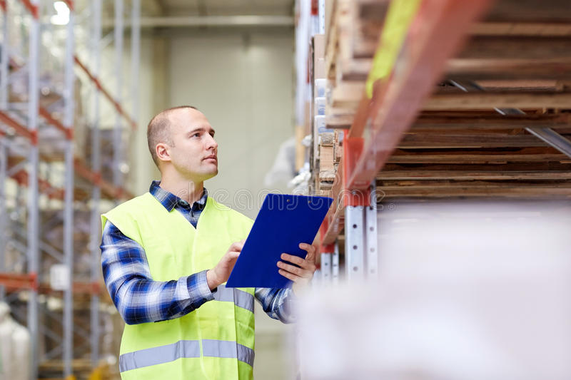 Man with clipboard in safety vest at warehouse. Wholesale, logistic, people and export concept - man with clipboard in reflective safety vest at warehouse royalty free stock images