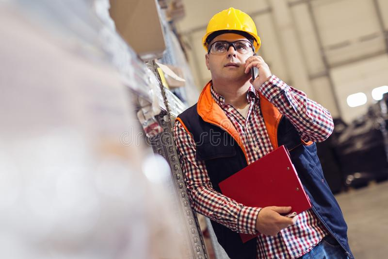 Man with clipboard and smart-phone at warehouse royalty free stock photos