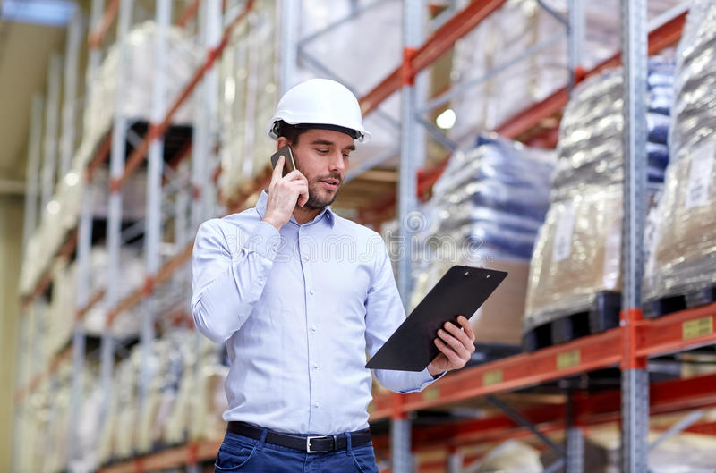 Man with clipboard and smartphone at warehouse royalty free stock photos