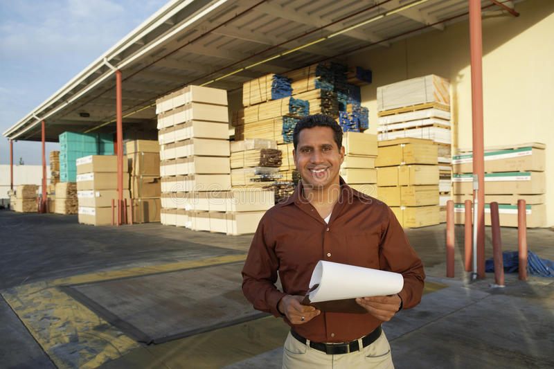 Man With Clipboard Standing In Front Of Timber Factory. Portrait of happy middle aged man with clipboard standing in front of timber factory stock photography