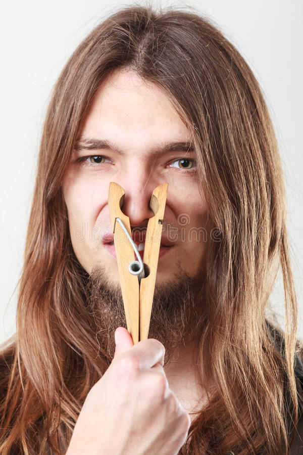 Man with clogged nose by clothespin stock image