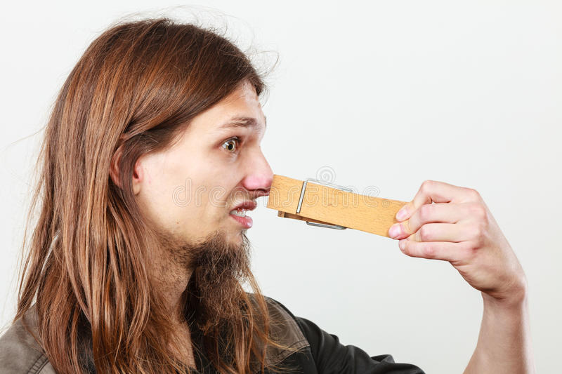 Man with clogged nose by clothespin royalty free stock image