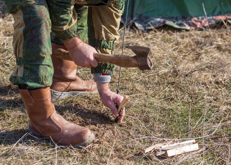 A man clogs a peg at a campsite.  stock images