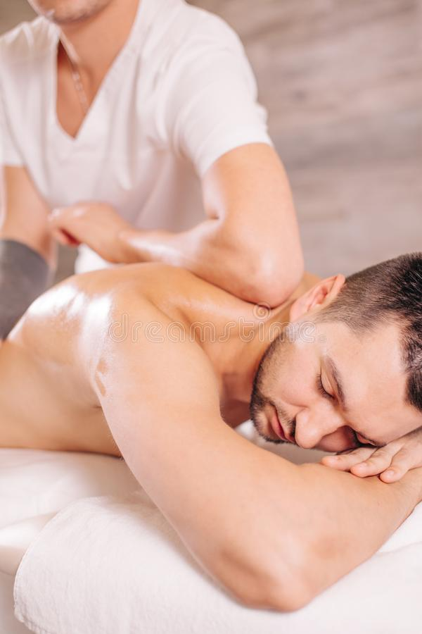 Man with closed eyes lying on the bed and getting massage for sore back royalty free stock photos