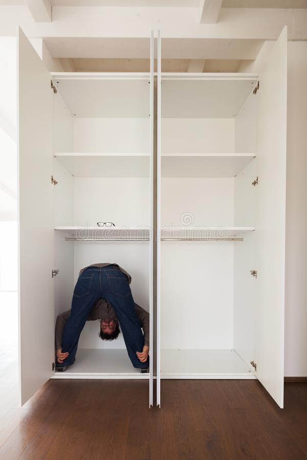Man in closet doing exercises, concept. Man in the closet does exercises to keep fit in a bizarre way. Concept of space stock photos
