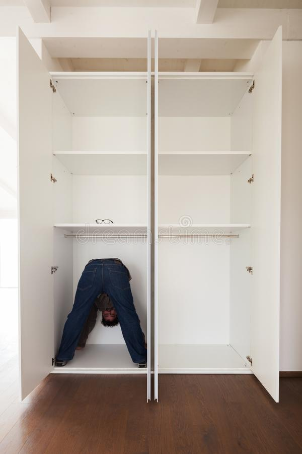 Man in closet doing exercises, concept. Man in the closet does exercises to keep fit in a bizarre way. Concept of space royalty free stock photos