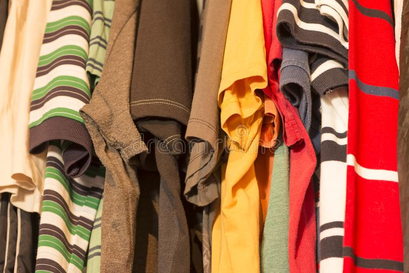 A Man closet. A man's closet with several t-shirts of various colors royalty free stock photo