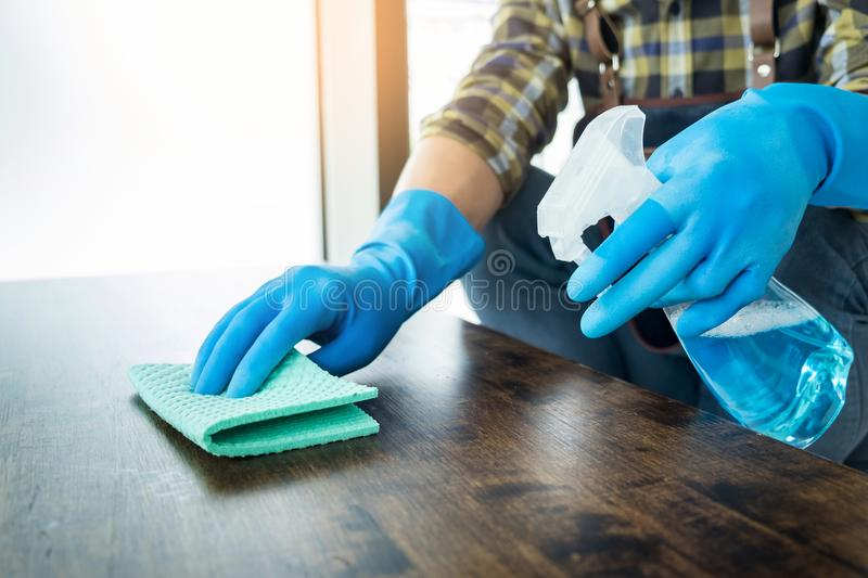 Man with cloth cleaning wooden table in home uses rag and fluid royalty free stock images